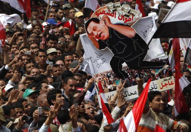 "Protesters hold up a caricature of ousted president Hosni Mubarak carrying ""people's money"" in Tahrir Square, Cairo, April 8, 2011. Tens of thousands of Egyptians protested in Cairo on Friday demanding the prosecution of Hosni Mubarak and accusing the military of being too slow to root out corruption from his era. REUTERS/Asmaa Waguih (EGYPT - Tags: POLITICS CIVIL UNREST) CREDIT: REUTERS PUBLISHED DATE: 04/08/2011"